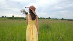 Mulher bonita no vestido que corre através do campo verde no movimento lento filme