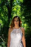 A mulher bonita, a noiva com olhos azuis e o cabelo marrom andam através das madeiras frondosas, floresta em um dia ensolarado br fotos de stock royalty free