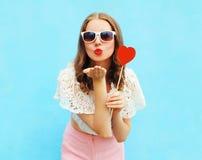 A mulher bonita nos óculos de sol com o pirulito vermelho do coração envia um beijo do ar sobre o azul colorido Fotografia de Stock Royalty Free