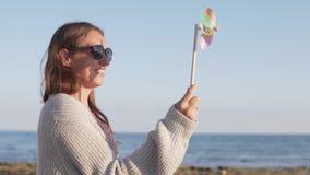 Mulher bonita nos óculos de sol nas férias de verão que jogam com moinho de vento do brinquedo filme