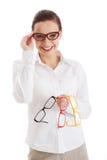 Mulher bonita nos monóculos que guardam três pares diferentes de ey Imagem de Stock Royalty Free