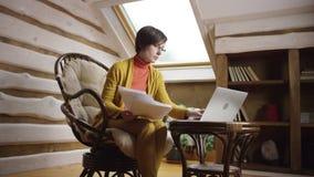 A mulher bonita nos vidros trabalha no portátil com documentos de papel vídeos de arquivo