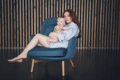 A mulher bonita nova abraça seu bebê recém-nascido imagens de stock
