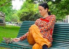A mulher bonita nova alimenta os pardais no parque Monceau, Paris imagens de stock royalty free