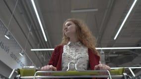 A mulher bonita nova anda através do supermercado vista do carrinho de compras vídeos de arquivo