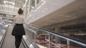 A mulher bonita nova aumenta em uma escada rolante reta filme
