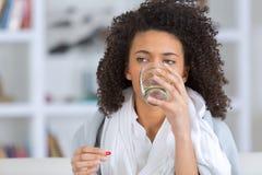A mulher bonita nova bebe a água do vidro foto de stock royalty free
