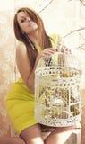 Mulher bonita nova brilhante que levanta com uma gaiola imagens de stock