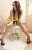 Mulher bonita nova brilhante que levanta com uma gaiola imagem de stock