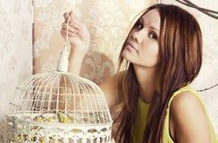 Mulher bonita nova brilhante que levanta com uma gaiola foto de stock royalty free