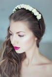 Mulher bonita nova com as flores no cabelo e nos olhos azuis Foto de Stock Royalty Free