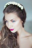 Mulher bonita nova com as flores no cabelo e nos olhos azuis Fotografia de Stock