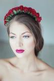 Mulher bonita nova com as flores no cabelo e nos olhos azuis Fotos de Stock Royalty Free
