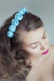 Mulher bonita nova com as flores no cabelo e nos olhos azuis Imagem de Stock