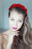 Mulher bonita nova com as flores no cabelo e nos olhos azuis Foto de Stock