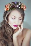 Mulher bonita nova com as flores no cabelo e nos olhos azuis Imagens de Stock