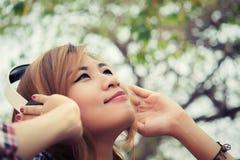 Mulher bonita nova com auscultadores escuta a OU alta da música fotografia de stock royalty free