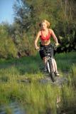 Mulher bonita nova com a bicicleta que atravessa a água pelo rio fotos de stock