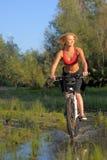 Mulher bonita nova com a bicicleta que atravessa a água pelo rio foto de stock royalty free