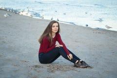 mulher bonita nova com cabelo longo, em calças de brim pretas e na camisa vermelha, sentando-se na areia na praia entre pássaros  Foto de Stock