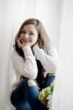 Mulher bonita nova com cabelo longo na camiseta e na calças de ganga que sentam-se perto da janela Foto de Stock Royalty Free