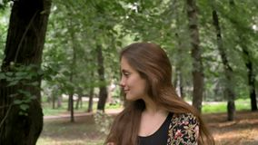 Mulher bonita nova com cabelo longo que anda no parque com árvores verdes e que sorri, feliz e alegre filme