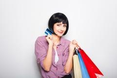 Mulher bonita nova com cartão e sacos de compras de crédito Fotos de Stock