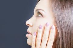 Mulher bonita nova com composição e tratamento de mãos bonitos, fundo preto Fotografia de Stock Royalty Free