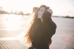 Mulher bonita nova com dança do cabelo encaracolado e luz solar longas da apreciação imagens de stock