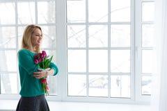A mulher bonita nova com grupo das tulipas, mola floresce, copyspace Imagens de Stock
