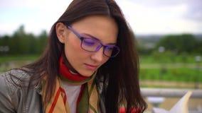 Mulher bonita nova com monóculos que lê um livro que senta-se em um banco fora em um parque no verão Feche acima da cara 4 vídeos de arquivo