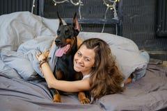Mulher bonita nova com o cão preto do doberman Foto de Stock Royalty Free
