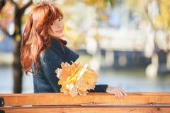 Mulher bonita nova com o cabelo vermelho que relaxa no parque do outono imagens de stock royalty free