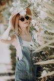 Mulher bonita nova com o chapéu, sentando-se perto dos arbustos cor-de-rosa na rua da cidade no verão foto de stock royalty free