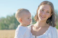 Mulher bonita nova com o filho pequeno do bebê em seus braços que sorri no campo de trigo no verão Fundo borrado da skyline fotografia de stock