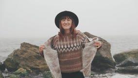 Mulher bonita nova com o lenço marrom grande que anda perto do mar filme