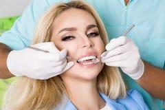 Mulher bonita nova com os dentes brancos bonitos que sentam-se em uma cadeira dental foto de stock