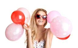Mulher bonita nova com os vidros que guardam os balões cor-de-rosa vermelhos, va Foto de Stock
