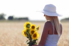 Mulher bonita nova com um chapéu em um campo com grama seca fotografia de stock