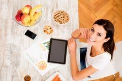 Mulher bonita nova com um PC da tabuleta em casa imagem de stock