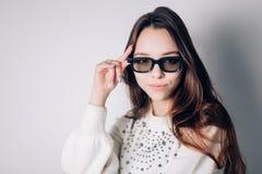 Mulher bonita nova com vidros 3d com um sorriso que olha a câmera Fotografia de Stock