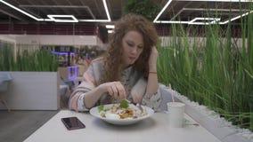 A mulher bonita nova come a salada de caesar em um café video estoque