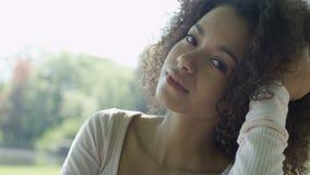 Mulher bonita nova da raça misturada com cabelo afro encaracolado que sorri felizmente em um parque verde filme