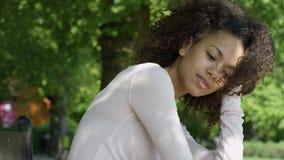 Mulher bonita nova da raça misturada com cabelo afro encaracolado que sorri felizmente em um parque verde
