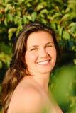 Mulher bonita nova de encontro às folhas verdes Imagens de Stock