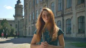 Mulher bonita nova do gengibre nos óculos de sol à moda que olham a câmera, sorrindo e pensando, construindo no fundo video estoque