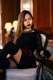 Mulher bonita nova elegante no vestido de seda lindo que senta-se dentro Foto de Stock Royalty Free