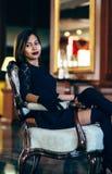 Mulher bonita nova elegante no vestido de seda lindo que senta-se dentro Fotografia de Stock