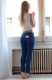 Mulher bonita nova em casa com telefone celular no bolso traseiro Imagem de Stock