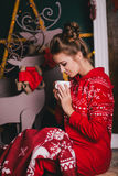 Mulher bonita nova em pijamas mornos vermelhos com os ornamento escandinavos que sentam-se perto da chaminé decorativa e do cacau Foto de Stock